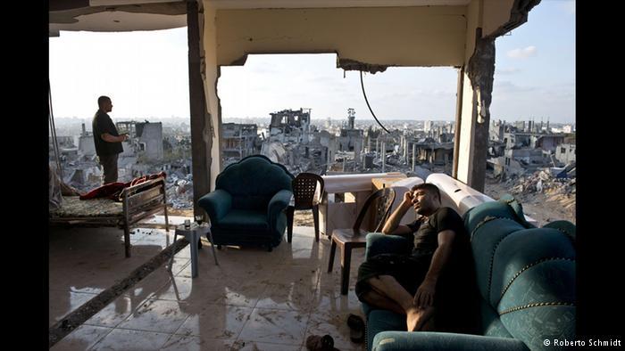 نمای ویران عکسی از شمال نوار غزه. محمد و عادل در خانه ویرانشده خود هستند. روبرتو اشمیت هنرمند عکاس مدتی با این دو زندگی کرده است. او حتی شبها نیز با آنها به خانه ویران شدهشان بازمیگشت. این دو نگران اثاثیه باقیمانده در خانهشان هستند.