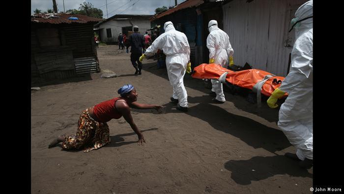 قارهی در حال زوال جان مور این عکس را از زنی گرفته که در غم خواهر از دست رفتهاش سوگواری میکند. خواهرش در پی ابتلا به بیماری ابولا درگذشته است. این عکس از مجموعه عکسهای سال ۲۰۱۴ جان مور انتخاب شده و موضوع آن